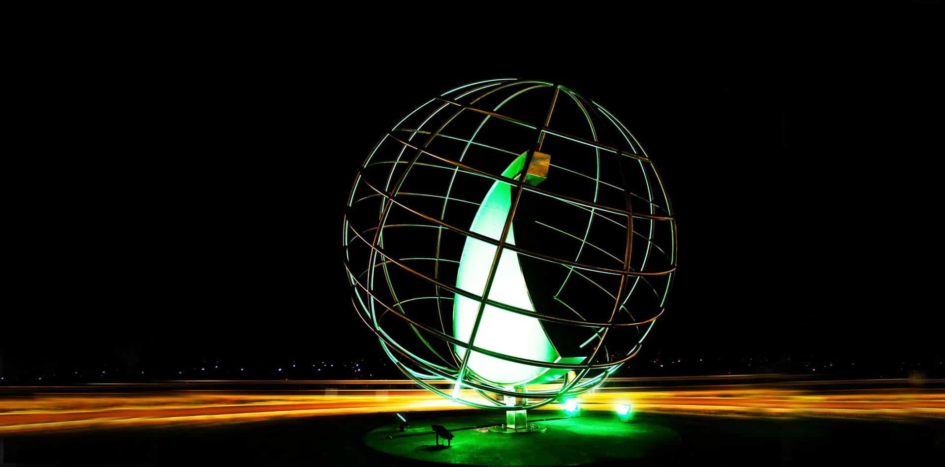 Kreisverkehrskulptur Hammerer Aluminium Ranshofen bei Nacht | Kugelform aus Alu-Stangen-Gitter mit grün beleuchteter Haiflosse | Svoboda
