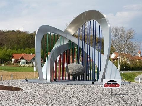 Kreisverkehrskulptur Gemeinde Sebersdorf/Bad Waltersdorf bei Tag | Alubögen mit bunten Stangen & Stein | Svoboda
