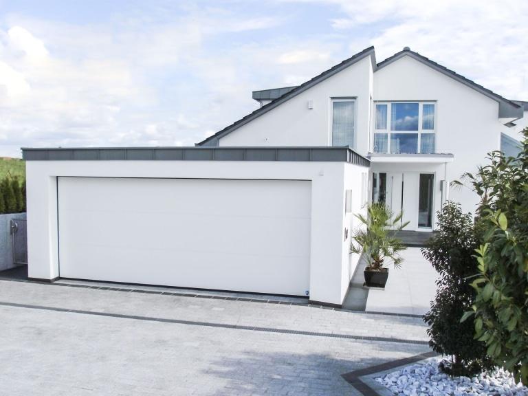 Pegasus Premium 04 | weißes Deckenstektionaltor bei Garage bei modernem, weißen Haus | Svoboda Metalltechnik