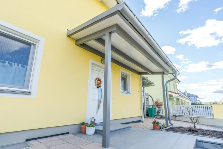 Vordach Alu 43 a | Graues Aludach bei Eingangstür mit weißer Paneeleindeckung, gelbes Haus | Svoboda