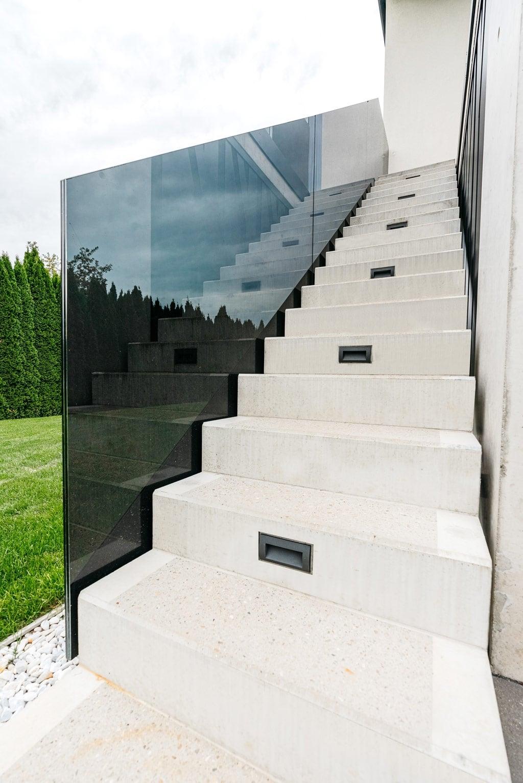 Augsburg 15 m | stirnseitiges Ganzglas Stiegengeländer mit Grauglas bzw. schwarzem Glas bei Betonstiege | Svoboda Metalltechnik