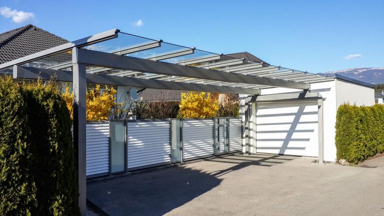 Carport 23 | grau aus pulverbeschichtetem Aluminium mit Klarglas-Eindeckung vor Garage | Svoboda Metalltechnik