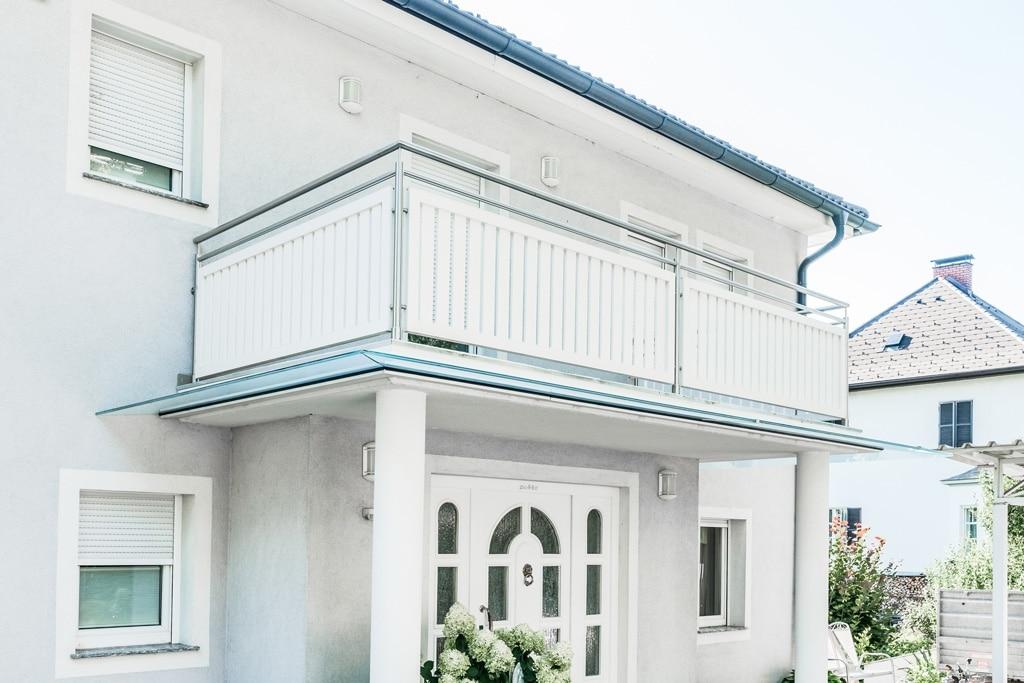 EA Baden 01 h | Balkongeländer mit Edelstahl-Rundrohr-Rahmen und weißem Alu-Innenfeld mit senkrechten Latten | Svoboda Metalltechnik