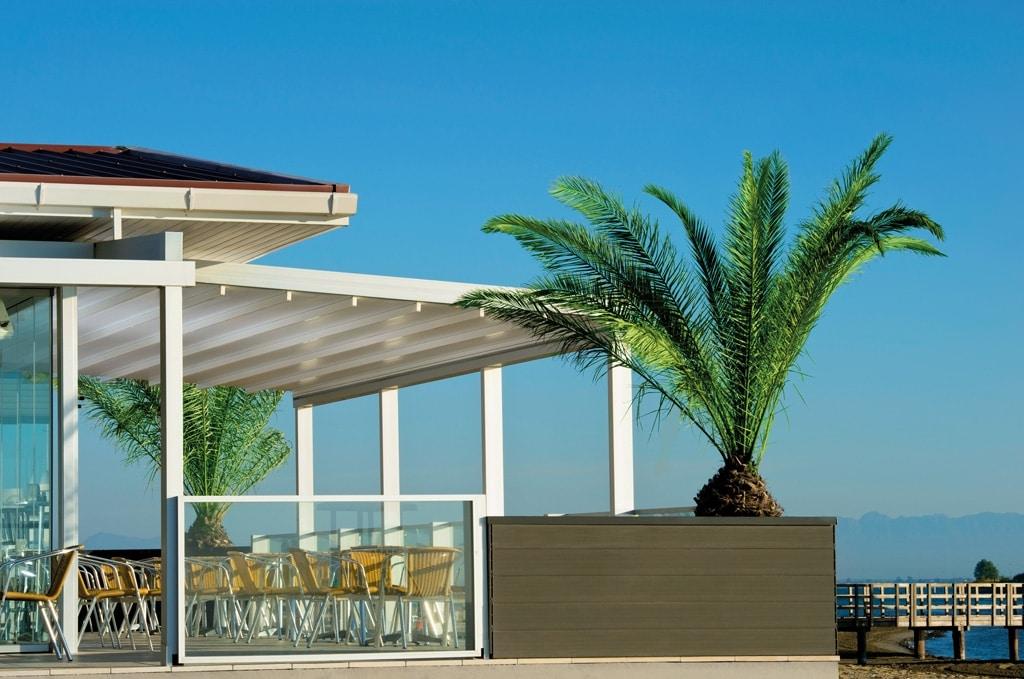 Level 01 c | weiße Schiebemarkise aus Aluminium weiß bei Gastroterrasse mit Palme am Meer | Svoboda