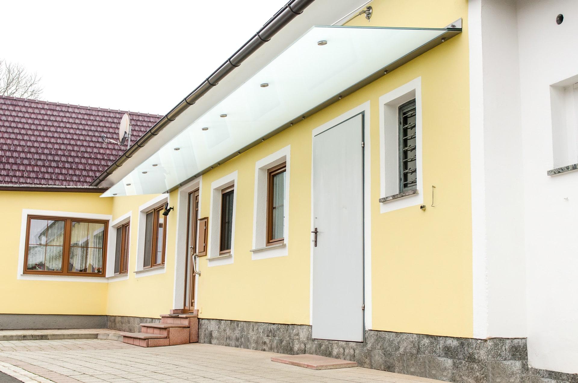 Nurglasvordach 16 a   langes Vordach aus Mattglas ohne Steher bei gelbem Haus   Svoboda Metall
