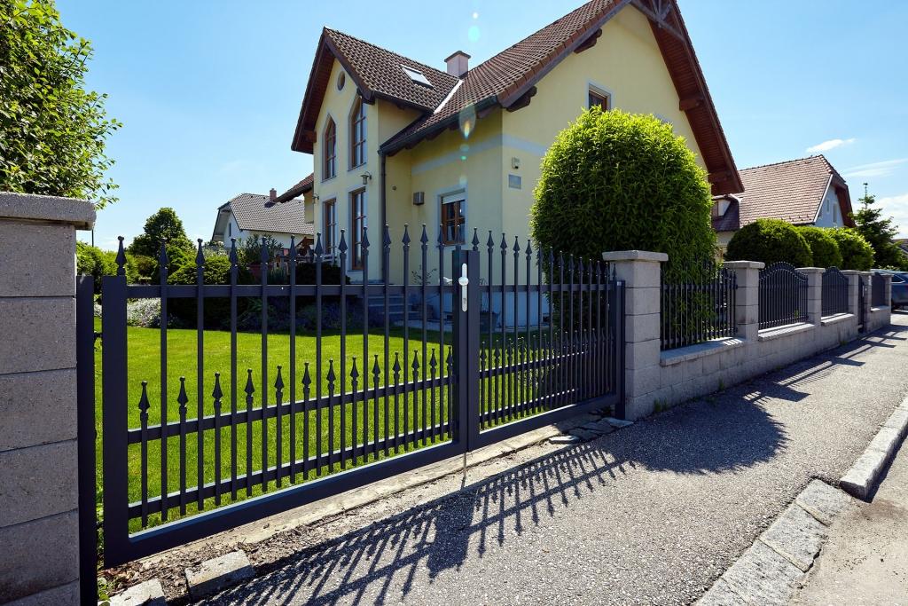 OZ 18854 | Schmiede-Alu-Doppel-Flügeltor schwarz mit Spitzen bei Gartenmauer, Haus gelb | Svoboda