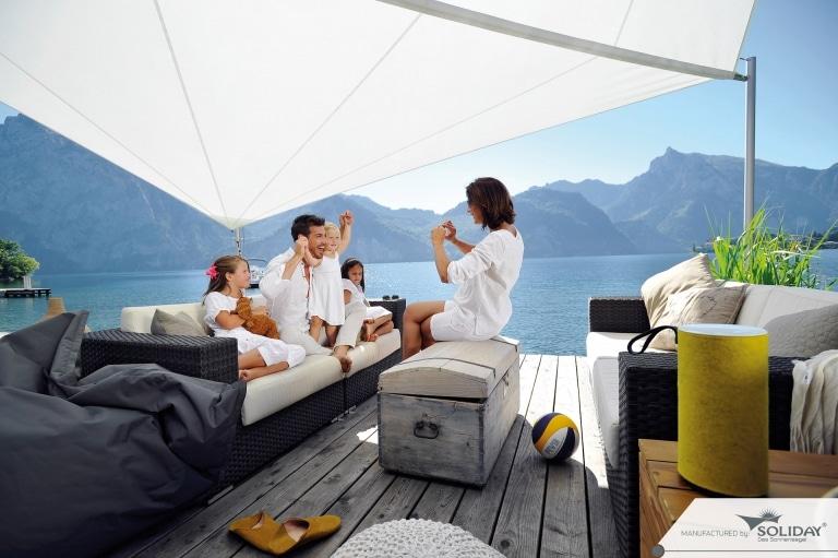 Sonnensegel A 01 c | Familie unter weißem Sonnenschutz-Sonnensegel am See | Svoboda Metalltechnik