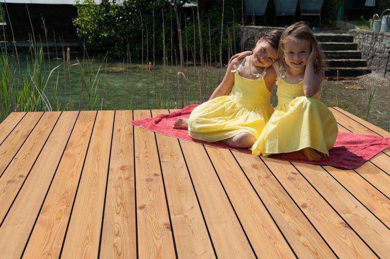 2 Mädchen auf Holzsteg bei Naturteich mit hellbraunen Holzbodendielen für den Außenbereich | Svoboda