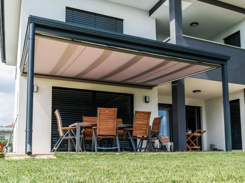 TM 11 a | offene Markise unter Glasdach montiert, Stoff rot, modernes grau-weißes Haus | Svoboda