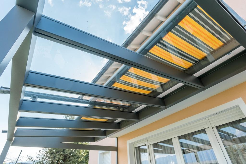 TM 12 d | Unteransicht gelb-grau-orange gestreifte Aufdachmarkise bei Aluminiumüberdachung | Svoboda