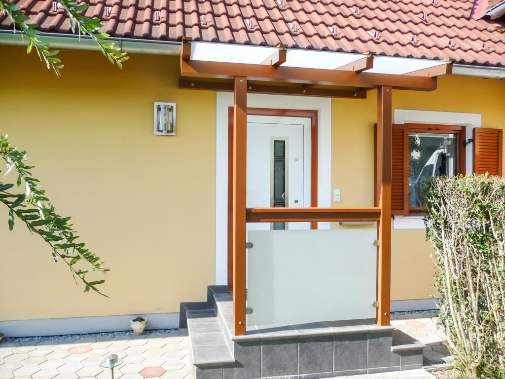 Vordach Alu 14 a | Eingangsdach aus Aluminium braun mit Mattglas, Glasgeländer bei Stehern | Svoboda