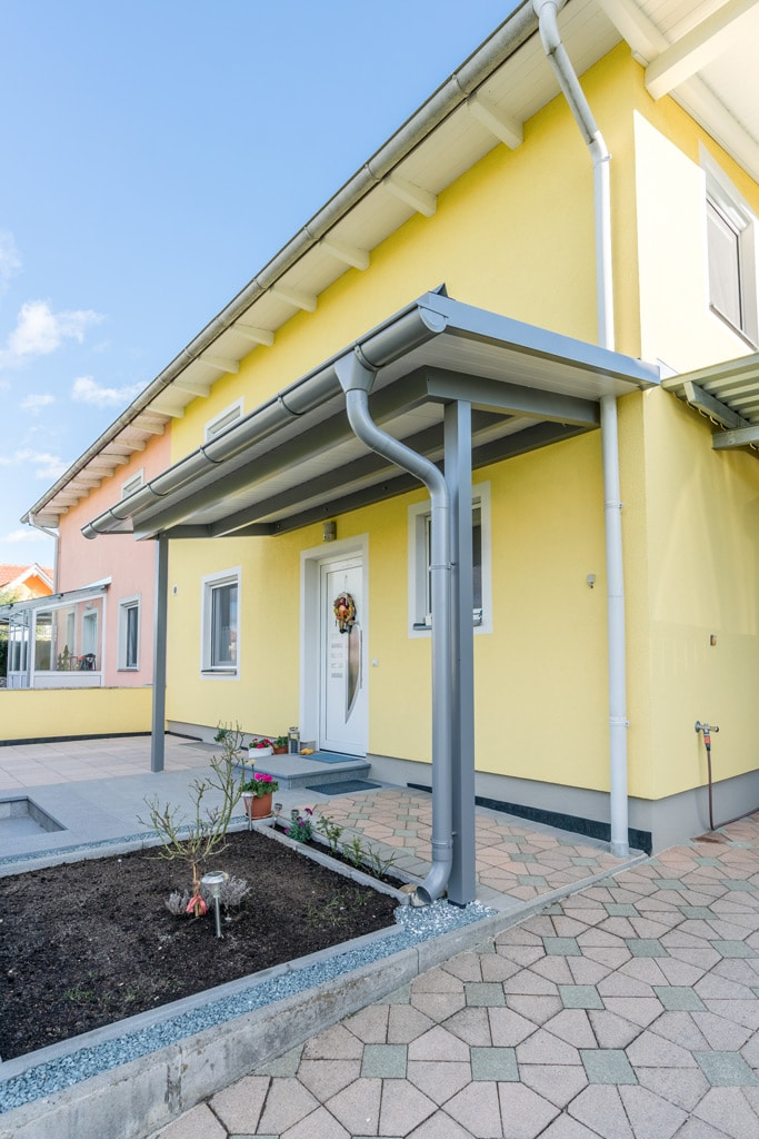 Vordach Alu 43 c | Alu-Vordach grau mit weißen Paneelen, Regenrinne & -Ablauf, Haus gelb | Svoboda