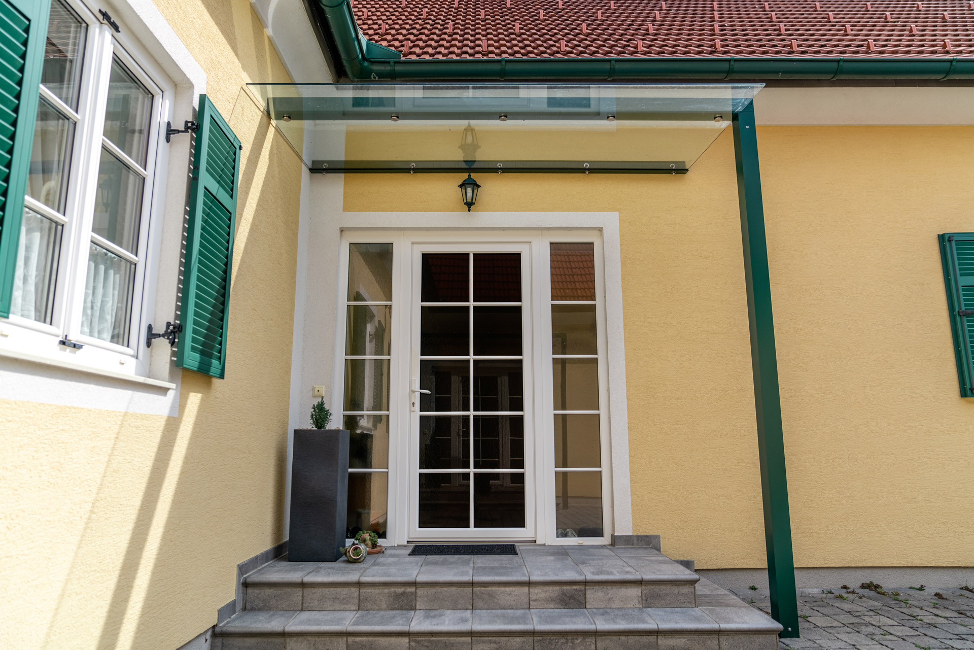 Vordach Alu 44 b | modernes Metall-Eingangsdach, mossgrün beschichtet mit Klarglas | Svoboda