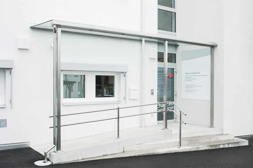 Vordach Niro 08 a | Eingangsdach Edelstahl bei öffenltichem Gebäude mit Rollstuhlrampe | Svoboda