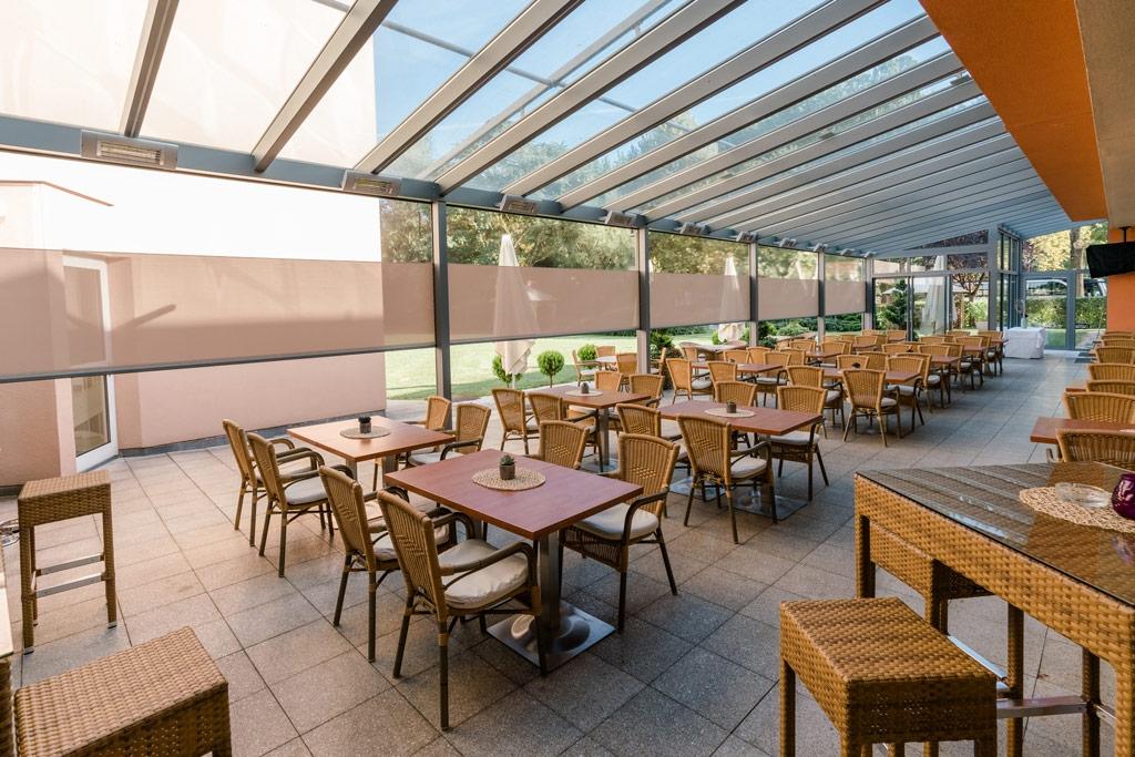 Z 14 e | Hotelterrasse mit Senkrechtmarkisen bei Alu-Dach, Stoff beigerosa mit Sichtfenster, halb offen | Svoboda