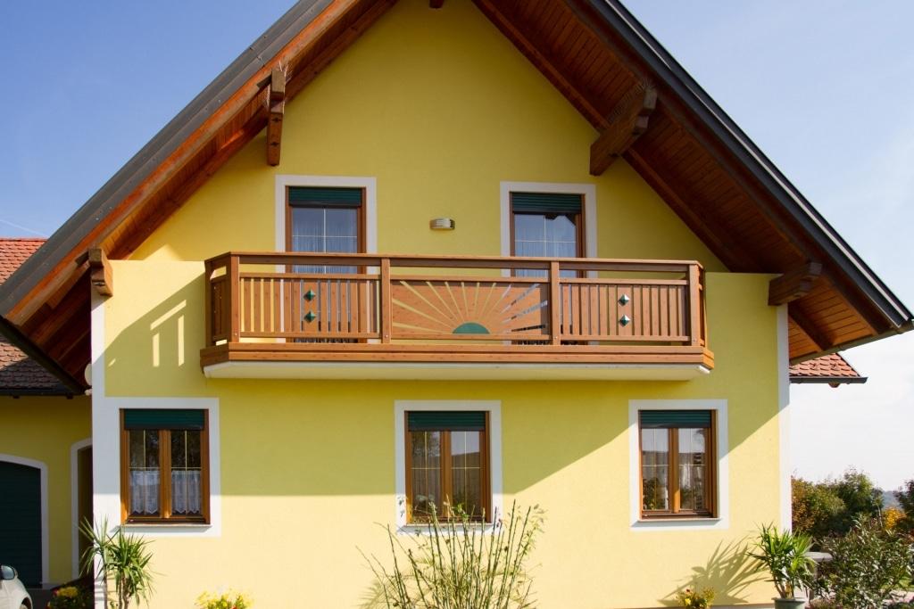 Amstetten 10 H a | klassicher Balkon mit Dekorsonne und senkrechten Latten bei gelbem Haus | Svoboda