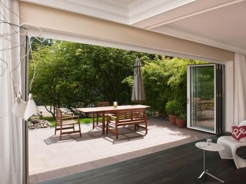 Faltwand 04 | Ansicht von Wohnzimmer auf Terrasse, geöffnete Falt-Elemente aus Glas | Svoboda