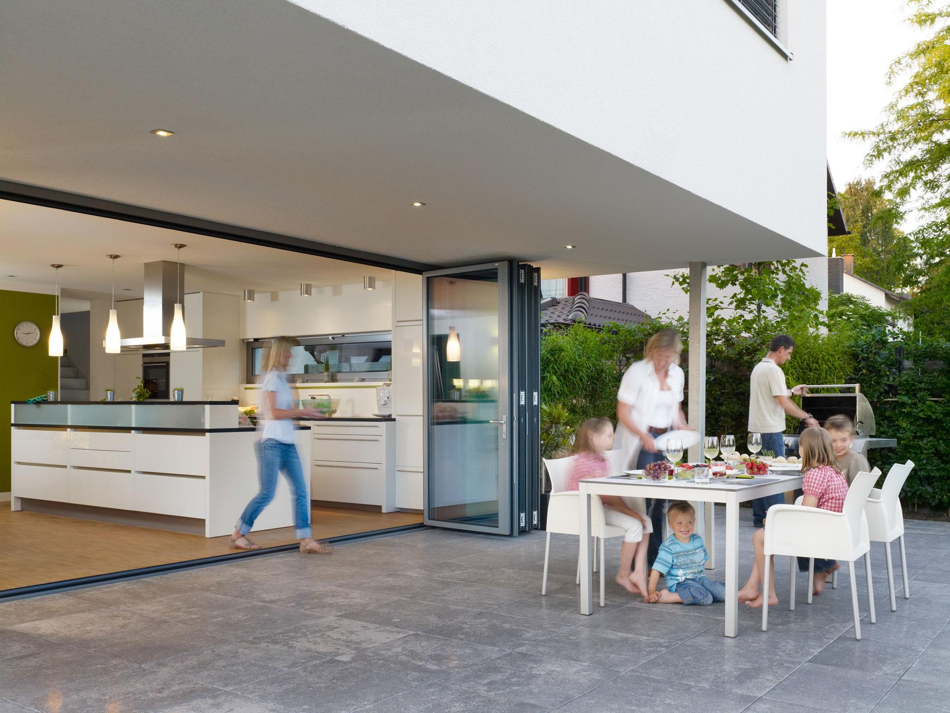 Faltwand 05 a | geöffnete Glas-Falt-Wand bei Küche auf Terrasse mit Familie am Esstisch| Svoboda