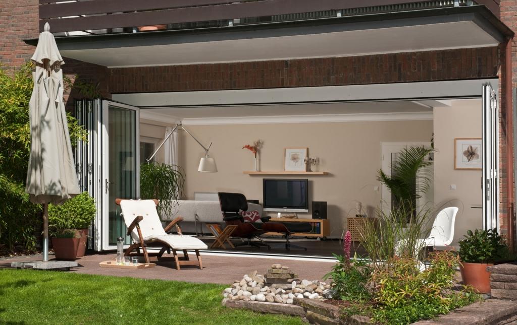 Faltwand 06   Wohnzimmer mit Glasfaltwand in Garten, Alurahmen weiß beschichtet, geöffnet   Svoboda Metalltechnik
