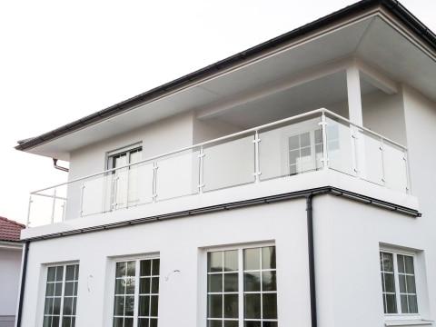 Schwechat 12 | Alubalkon Rundrohr mit Glas auf Boden montiert, weißes Haus| Svoboda Metalltechnik