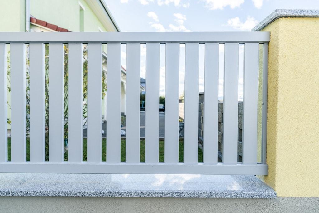 ZA Baden 14 e   grauer Aluzaun mit senkrechten Latten bei Gartenmauer   Svoboda Metalltechnik