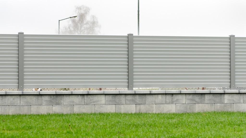 ZA Dürnstein 04 f | hellgraue Alu Einzäunung aus waagrechten Lamellen auf Mauer | Svoboda Metall