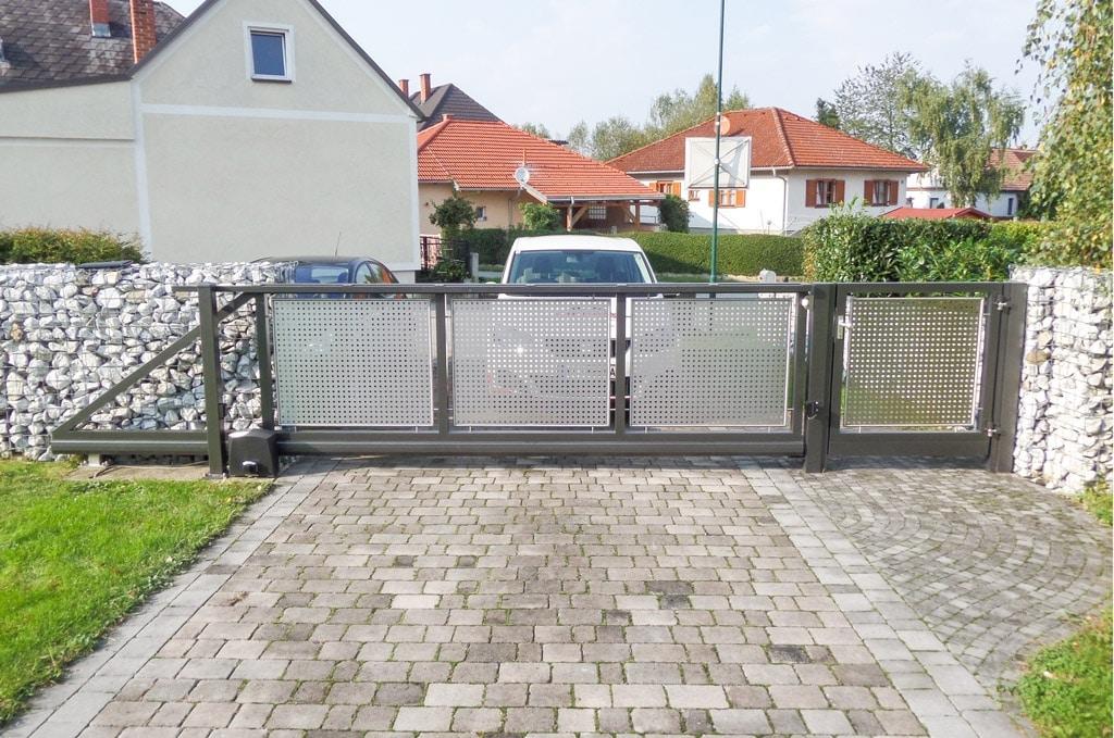 ZA Güssing 07 b | elektrisches Einfahrtstor aus grauem Alu mit gelochtem Edelstahl-Blech | Svoboda