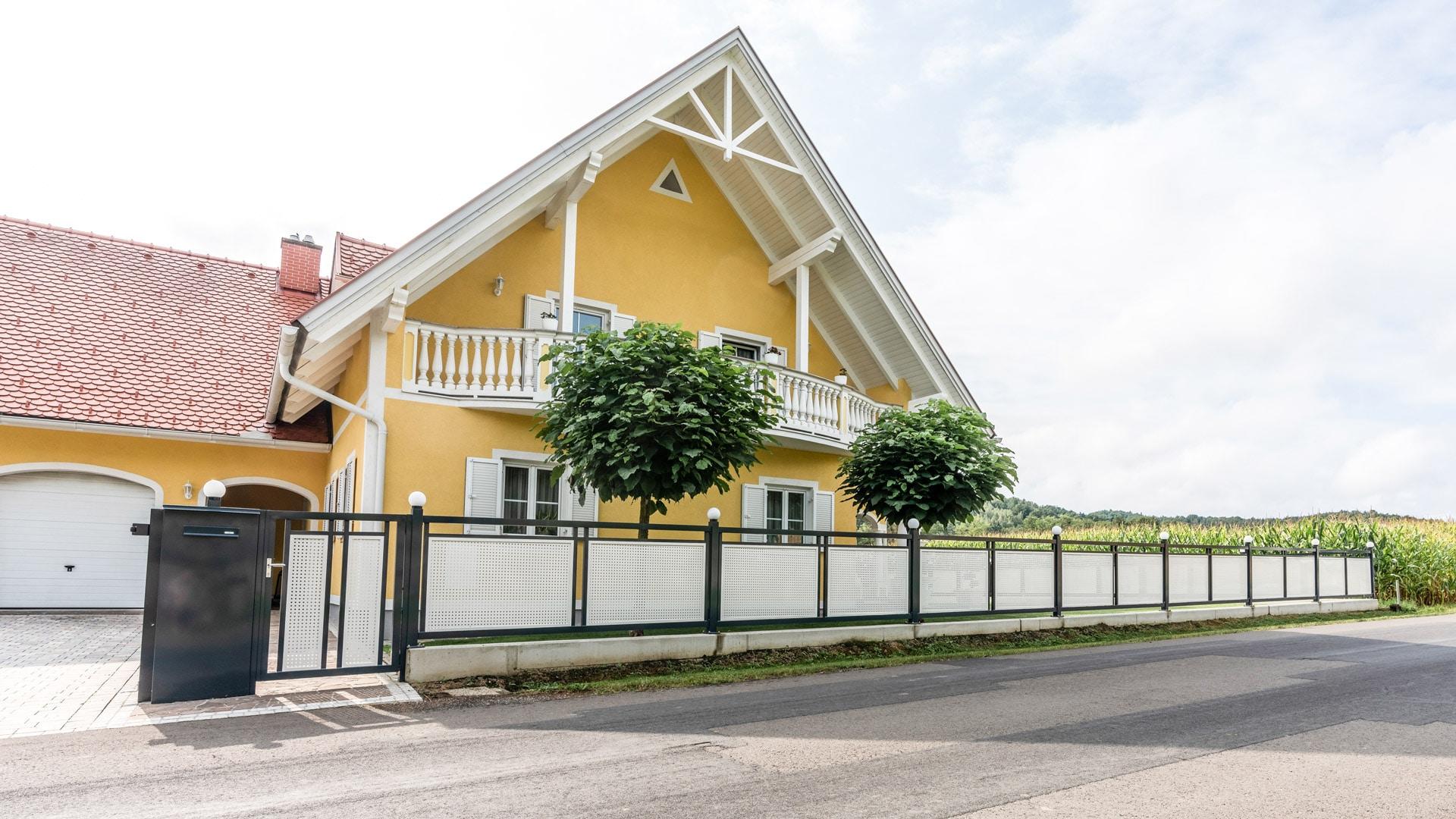 ZA Güssing 13 h   Alu-Zaunanlage anthrazit, Alu-Lochblech weiß, Haus gelb mit Balustraden   Svoboda