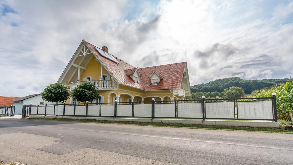 ZA Güssing 13 j   Zaunanlage aus Aluminium anthrazit mit weißem Lochblech bei gelbem Haus  Svoboda