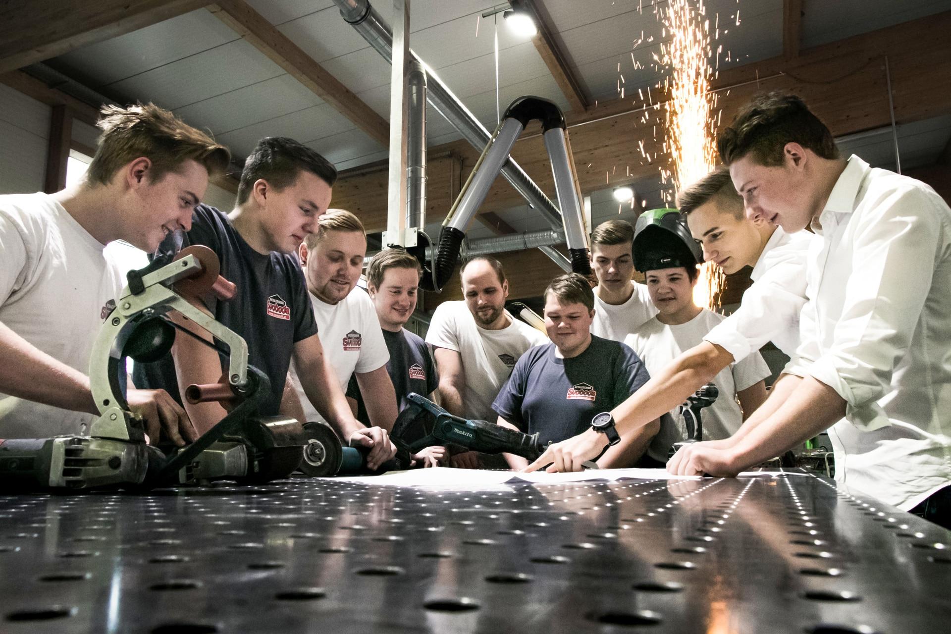 Lehrlinge Metalltechnik/Konstrukteure/technische Zeichner um Schweißtisch bei Plangespräch| Svoboda