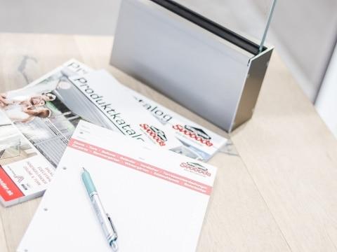 Kataloge und Block mit Stift neben Aluminiumbodenprofil für Nurglasgeländer | Svoboda Metalltechnik