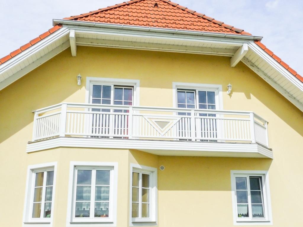 Gmunden 04 b | weißer Alu Lattenbalkon mit Dekor bei gelbem Haus mit Krüppelwalmdach | Svoboda