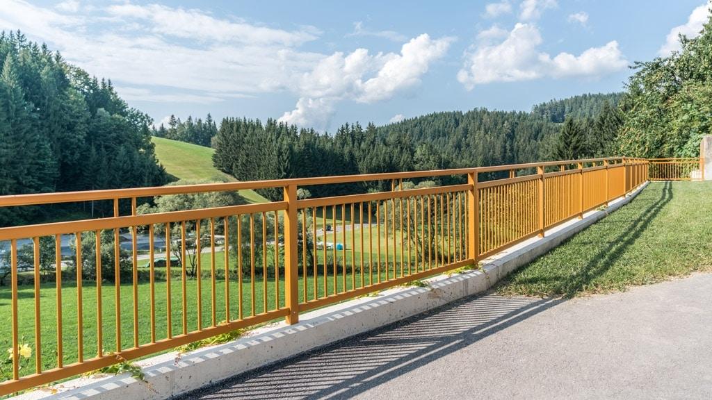 Graz 11 d | Absturzsicherung braun auf Mauer aus Aluminium mit vertikalen runden Alustäben | Svoboda