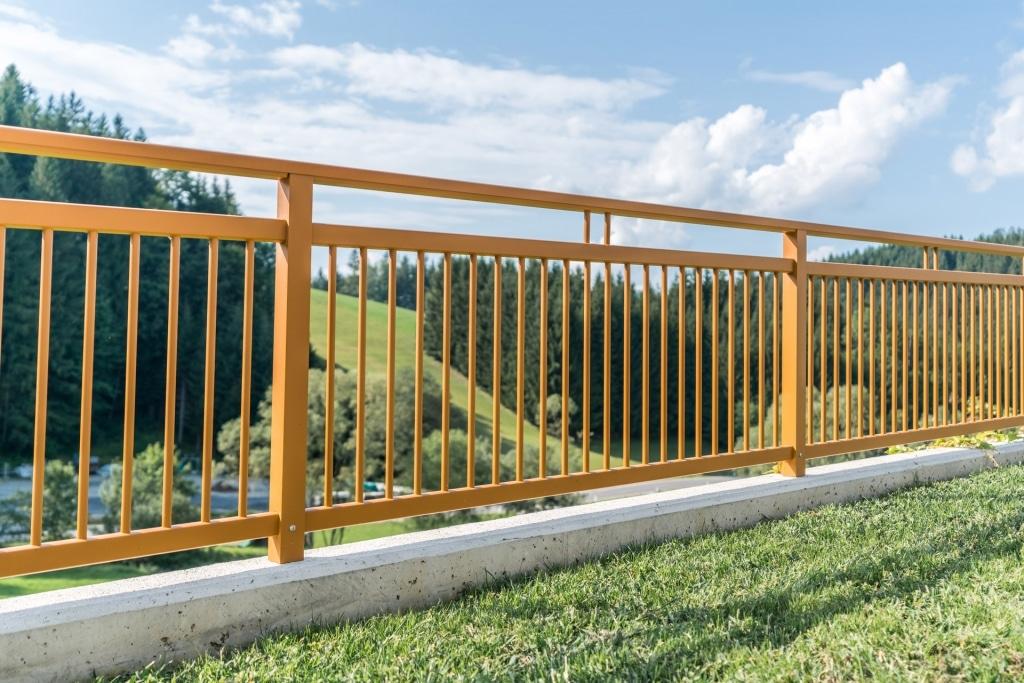 Graz 11 e | ockerbrauner Aluminium-Balkon mir senkrechten Alu-Stäben bei eckigen Stehern | Svoboda