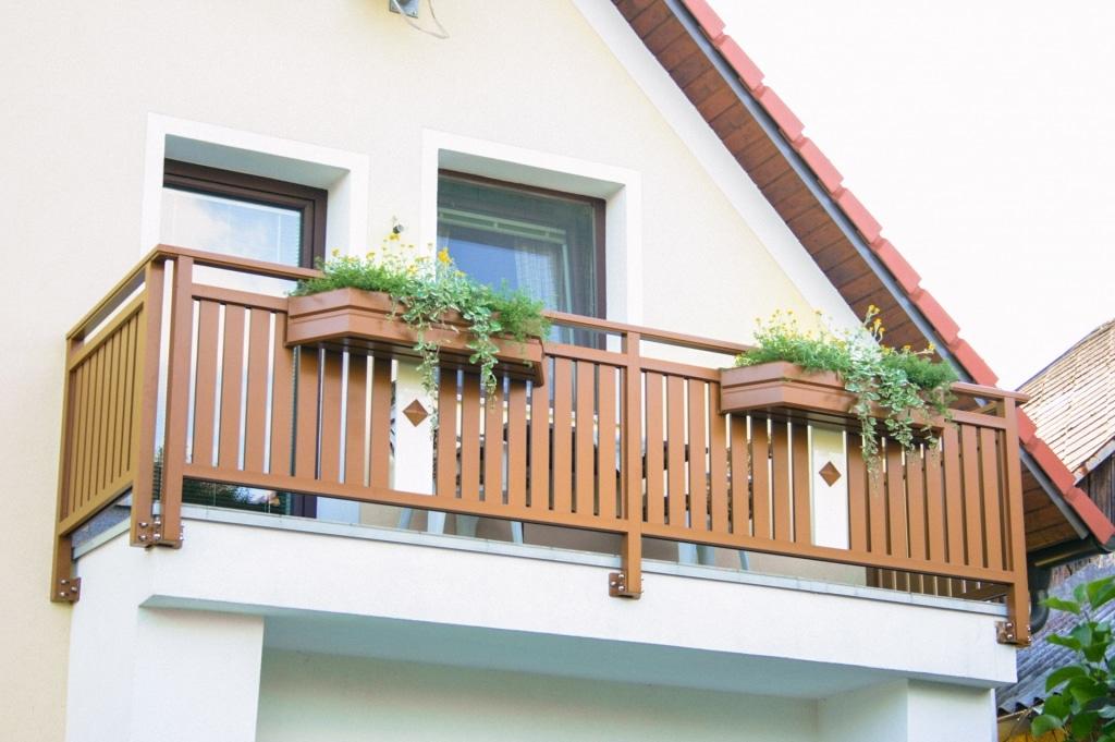 Lustenau 11 | Stirnseitig montierter Aluminiumbalkon braun mit Latten, Knopf, Blumenkisten | Svoboda