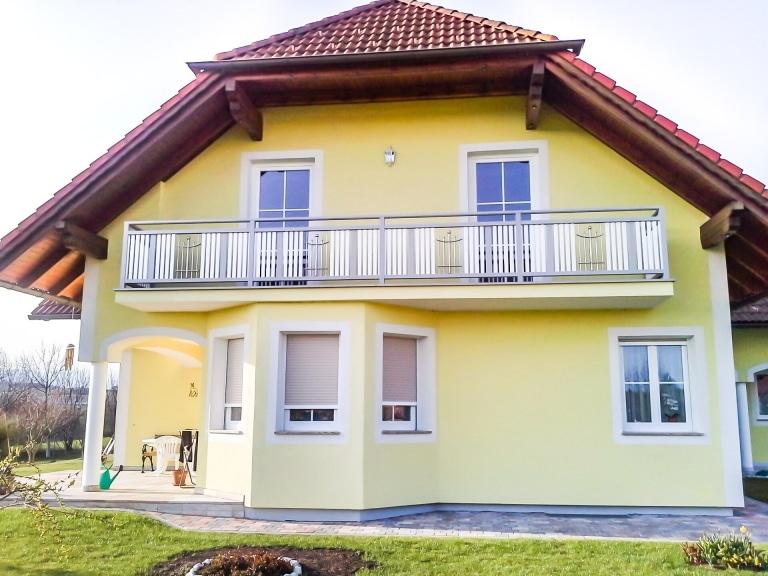 Melk 02 a   grau weißer Aluminiumbalkon mit Niro Dekor bei gelbem Haus mit Krüppelwalmdach   Svoboda