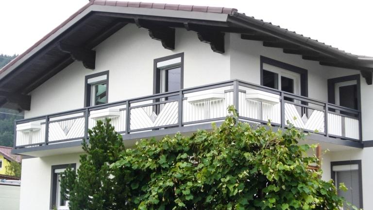 Saalfelden 04 a   grau-weißer Balkon mit Edelstahl Dreieck mit Stäben und Stein gefüllt   Svoboda