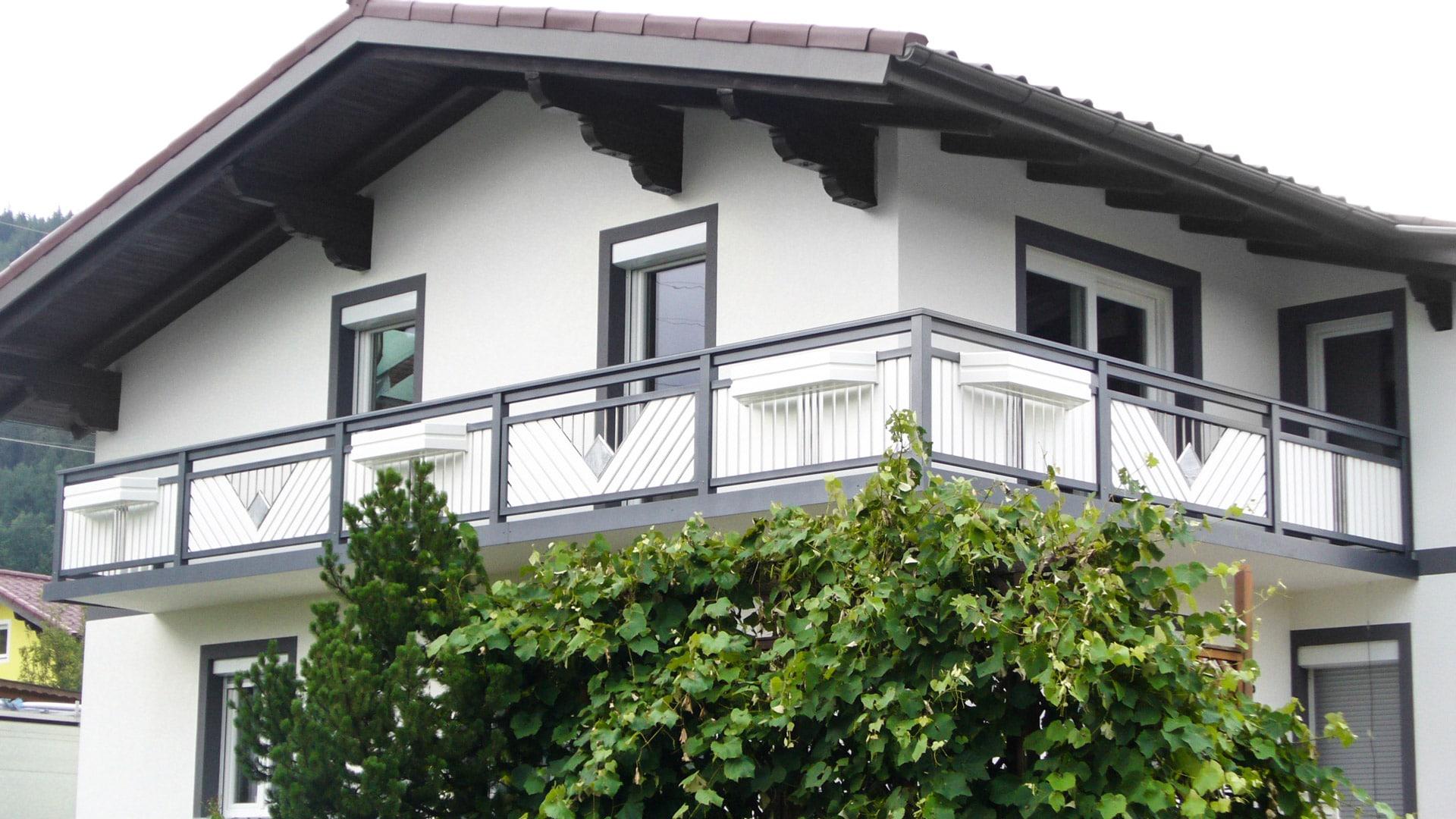 Saalfelden 04 a | grau-weißer Balkon mit Edelstahl Dreieck mit Stäben und Stein gefüllt | Svoboda