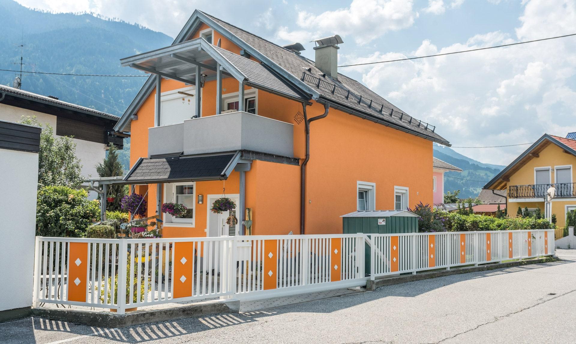 ZA Kriegalch 11 a   orange-weiße Alu-Zaunanlage mit automatischem Schiebetor bei Einfahrt   Svoboda