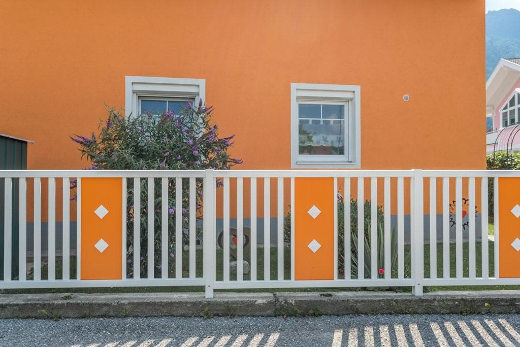 ZA Krieglach 11 c   Zaun mit Alu-Latten senkrecht weiß, Blech mittig orange mit 2 Knöpfen   Svoboda