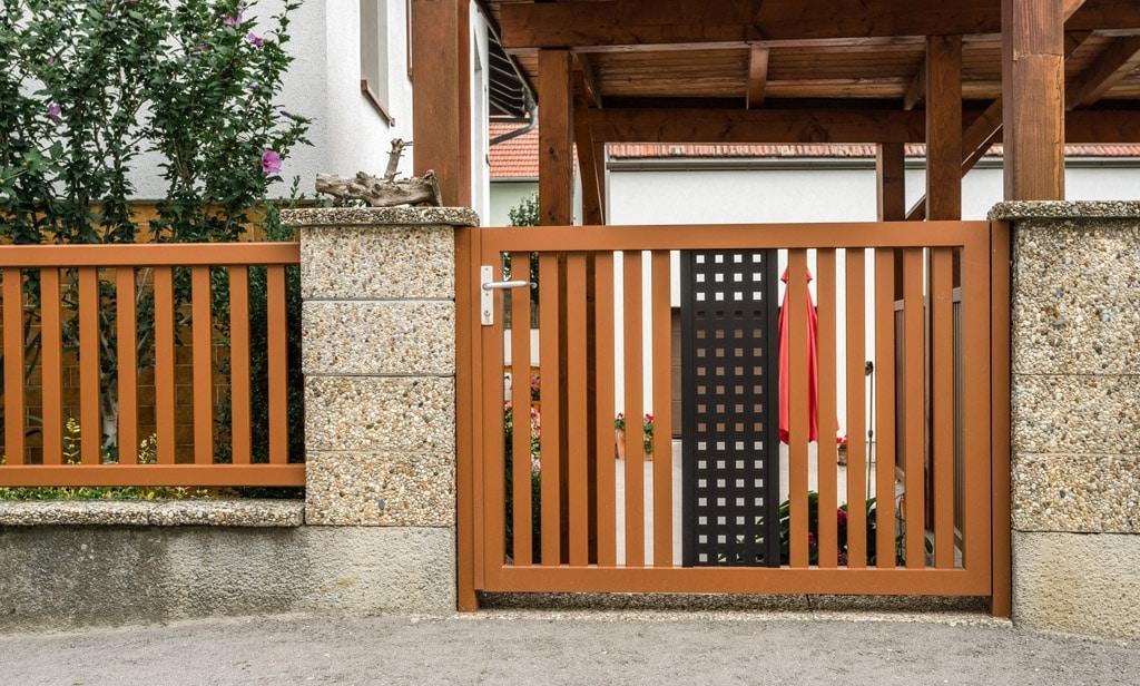 ZA Krieglach 12 g | Gehtür aus Aluminium bei Gartenmauer, Latten braun, Lochblech schwarz | Svoboda
