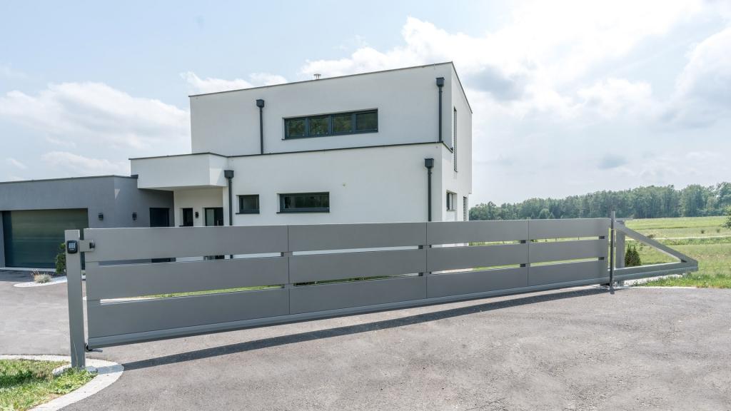 ZA Sonder 06 a | modernes Aluminium Schiebetor grau mit breiter Lattung bei modernem Haus | Svoboda