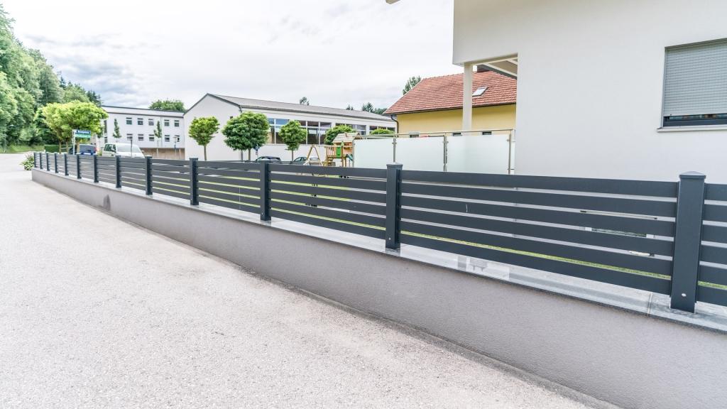 ZA Telfs 08 e | Aluminium-Einzäunung auf Gartenmauer mit anthrazitgrauer Querlattung | Svoboda