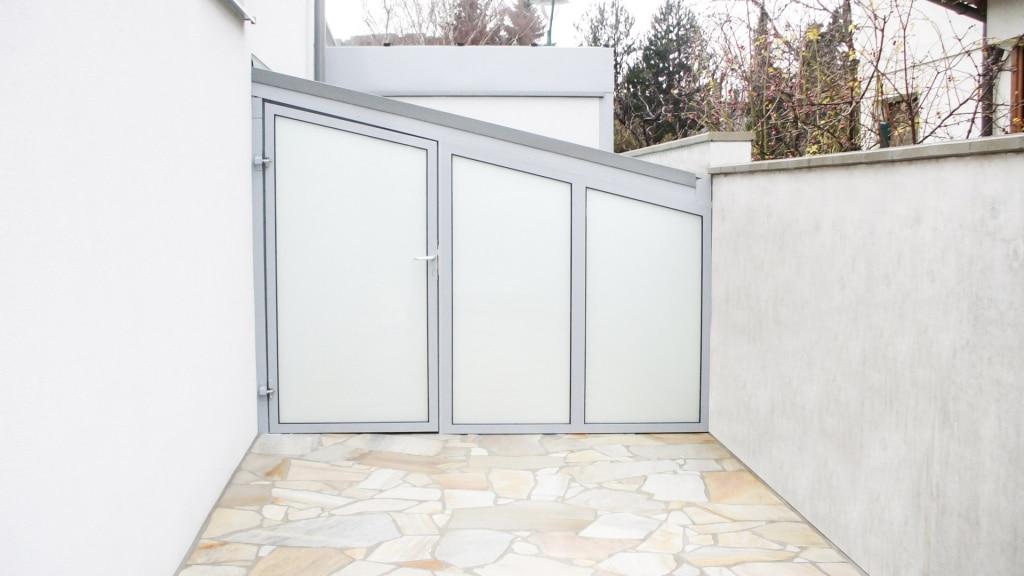 S 01 b | Geräteeinhausung aus grauem Alu und Fixglas mit Tür zwischen Haus und Gartenmauer | Svoboda