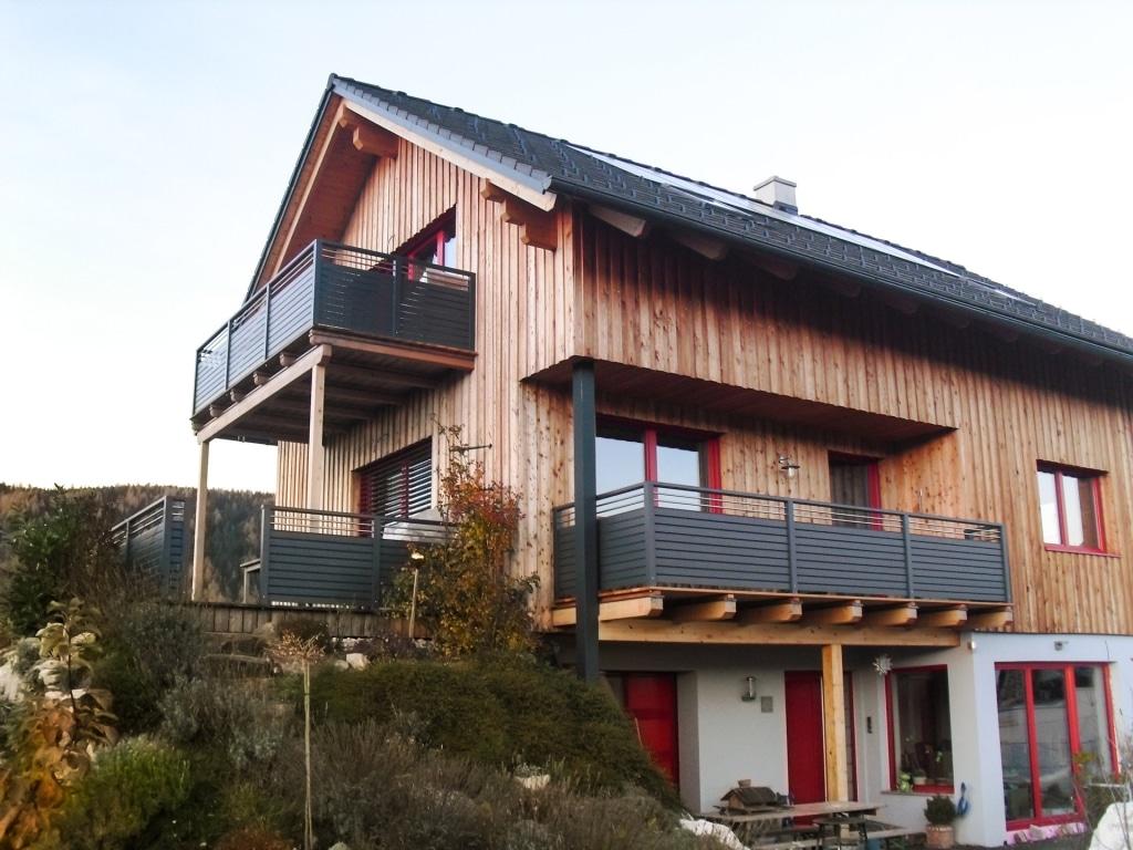 Telfs 06 | Moderner Alubalkon mit Querlattung grau und Nirostäben bei Haus mit Holzfassade | Svoboda