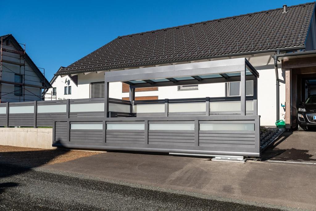 S 36 h | Müllüberdachung aus grau beschichtetem Aluminium mit Zaun & Schiebetor kombiniert | Svoboda