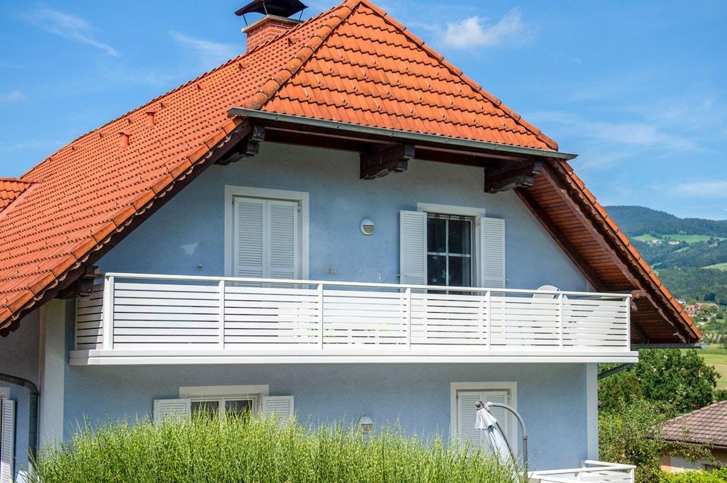 Telfs 12 e   Moderner, weißer Alubalkon mit waagrechten Alu-Latten, blaues Haus, Dach rot   Svoboda